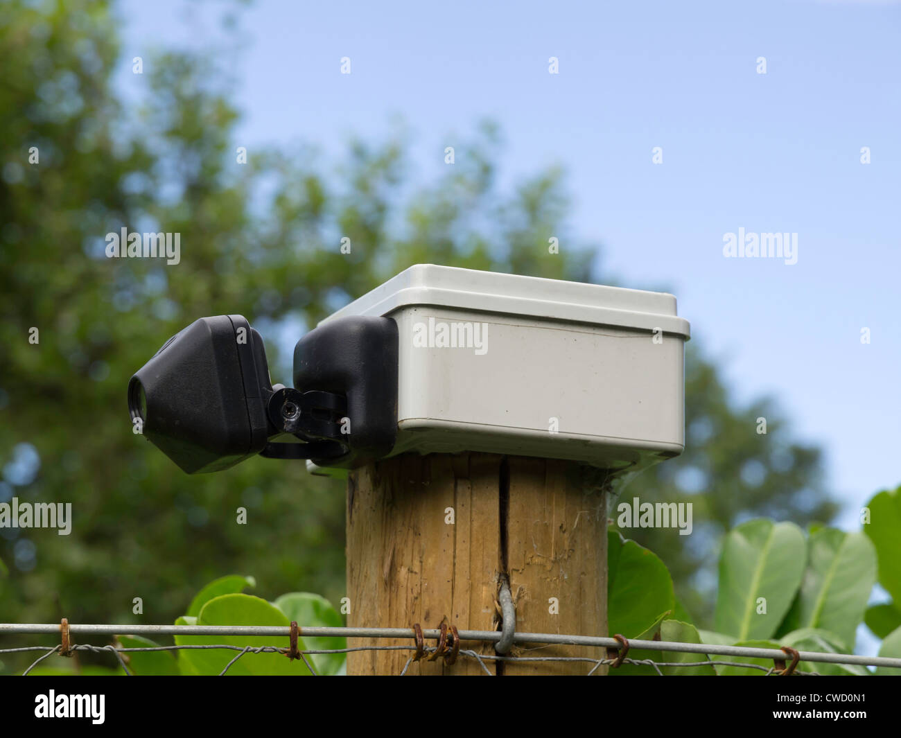 A small cctv security camera mounted on fence post in