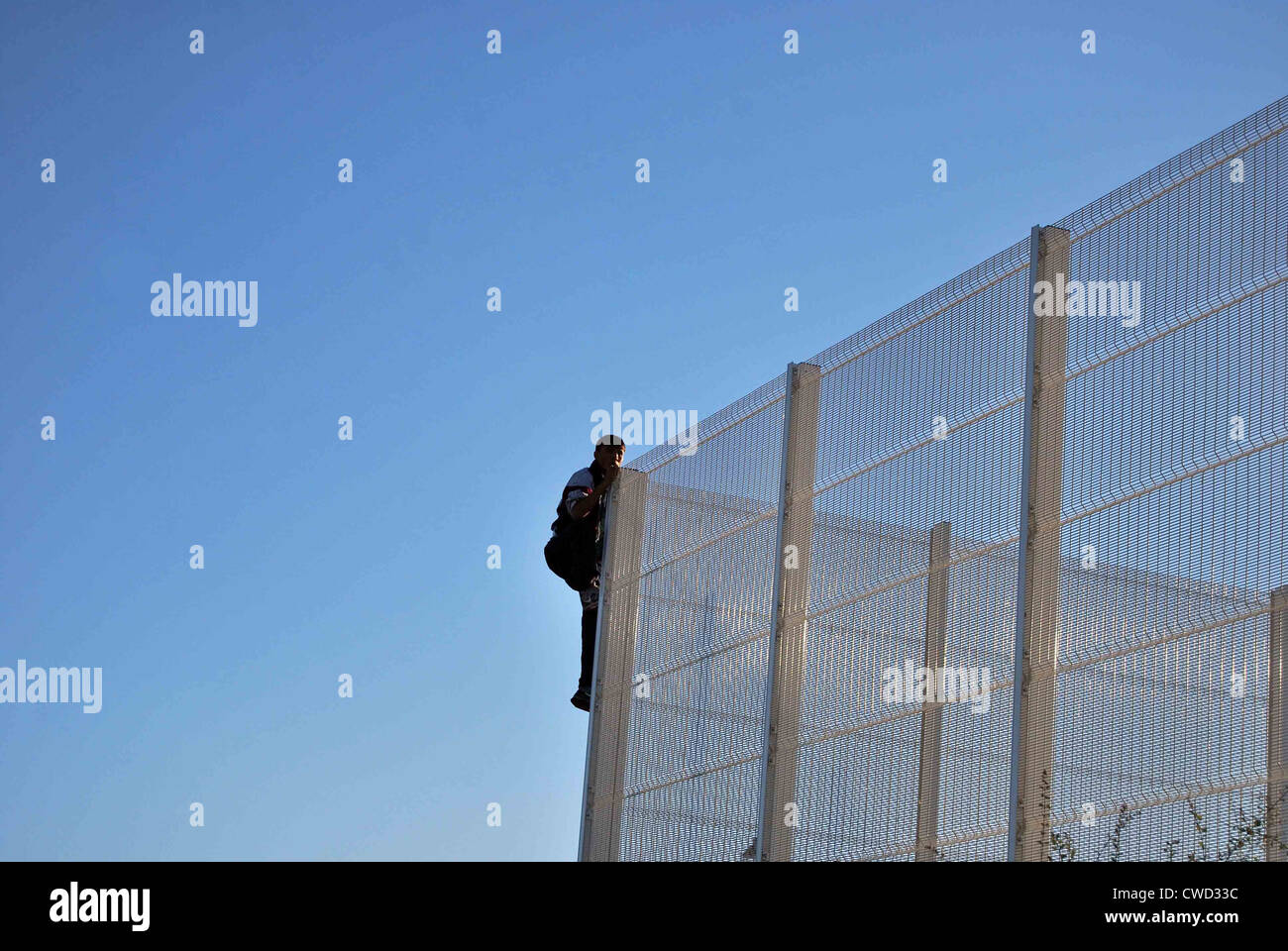a migrant in calais climbs a security fence to get into the port of calais and possibly into the uk