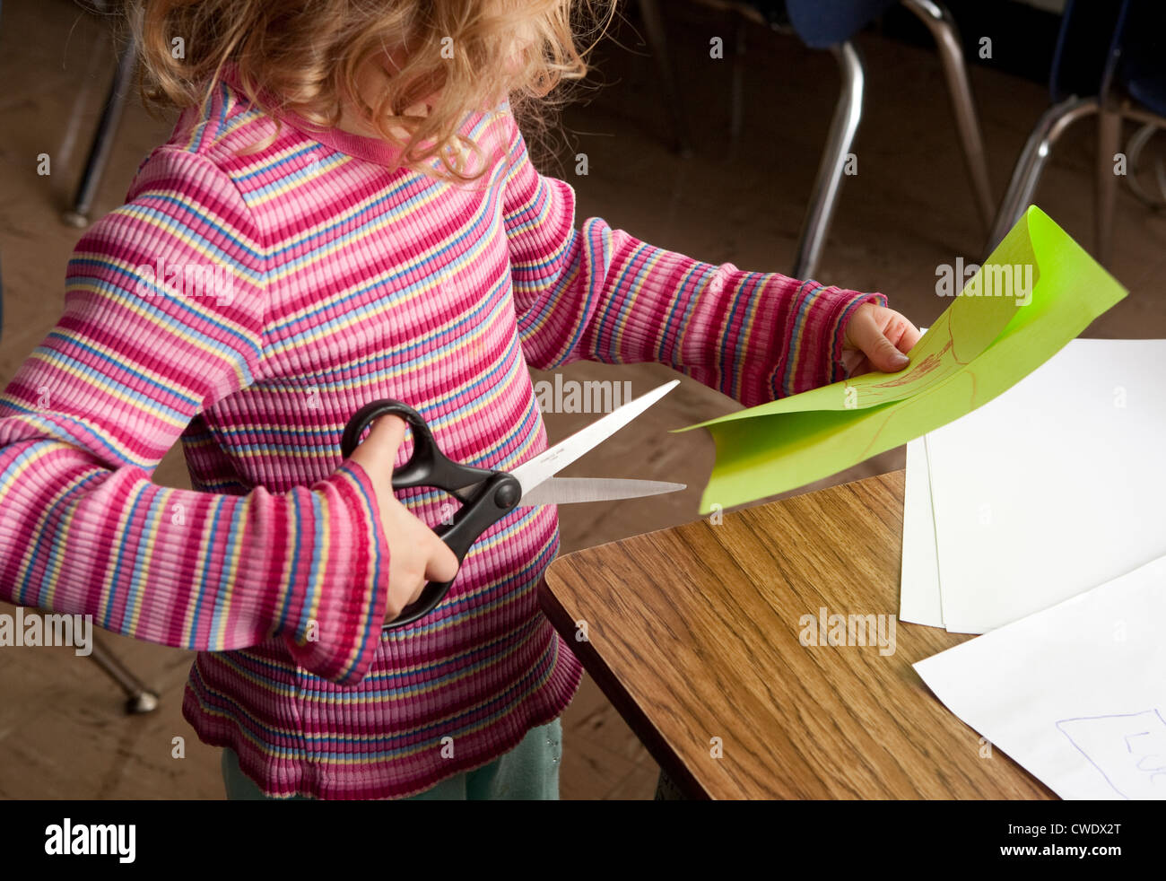 young white year old girl in colorful sweater uses large stock photo young white 5 year old girl in colorful sweater uses large dangerous scissors to cut through green paper out supervision
