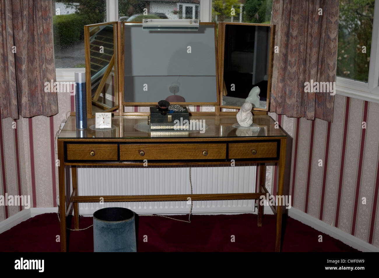 Bedroom dressing table with mirror - A Dressing Table With Mirrors In A Bedroom By A Bay Window With A Necklace Case Thermometer Aerosol And Statue