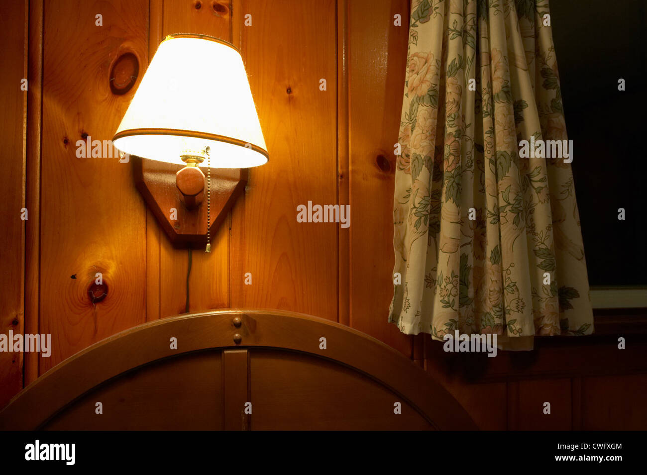 Shaded lamp on a wood paneled wall with curtains stock photo shaded lamp on a wood paneled wall with curtains mozeypictures Gallery