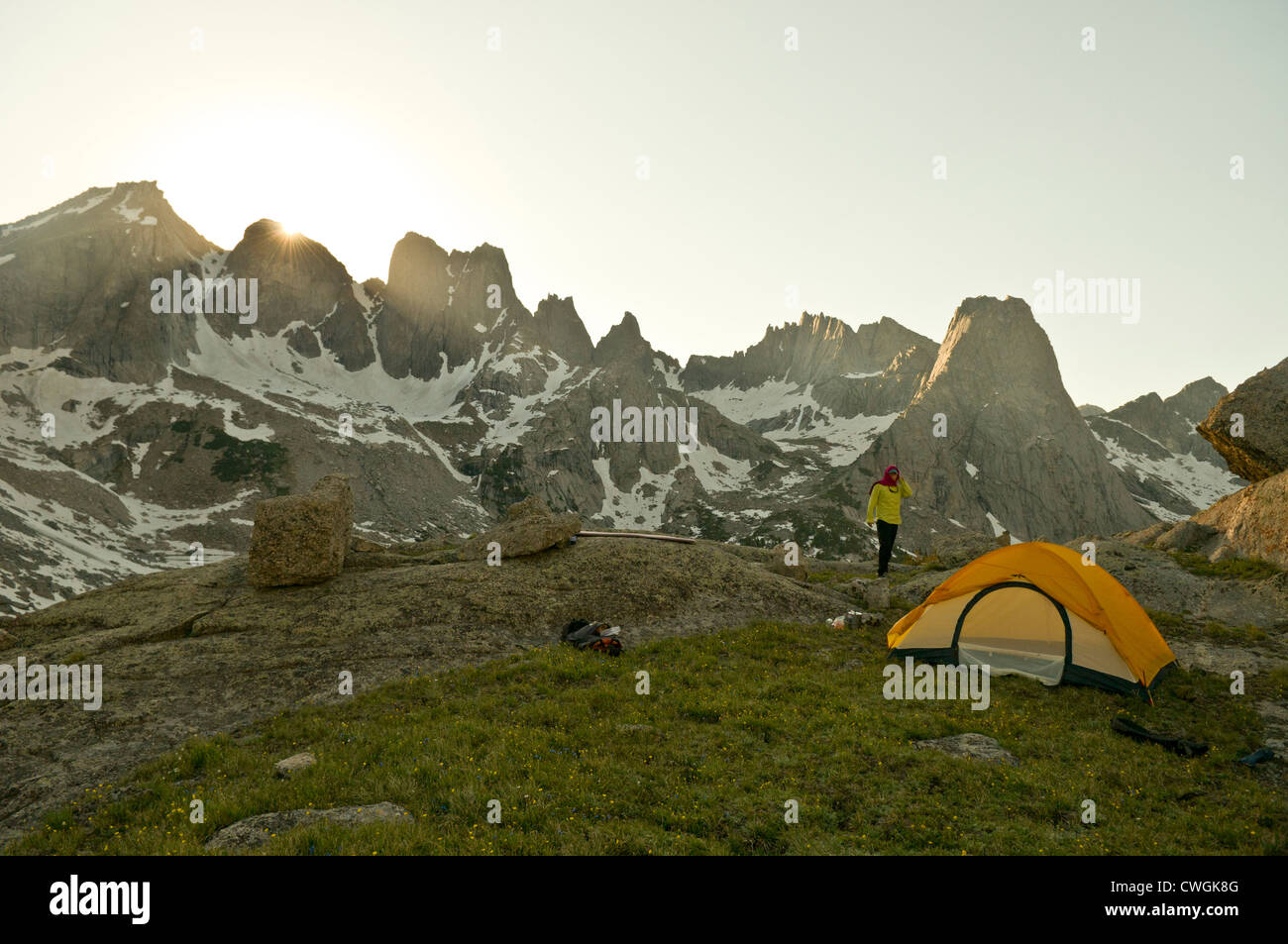 A woman standing next to tent at sunset Cirque of Towers Wind River Range Pinedale Wyoming & A woman standing next to tent at sunset Cirque of Towers Wind ...