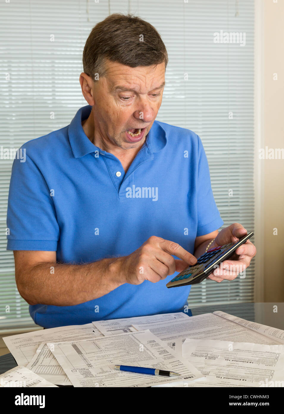 Senior caucasian man preparing tax form 1040 for tax year 2012 stock senior caucasian man preparing tax form 1040 for tax year 2012 showing shock at amount of tax owed falaconquin