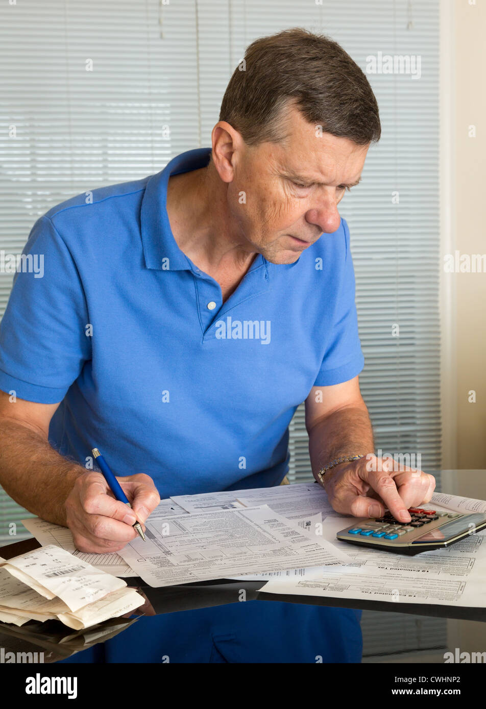 Senior caucasian man preparing tax form 1040 for tax year 2012 with senior caucasian man preparing tax form 1040 for tax year 2012 with receipts and calculator falaconquin