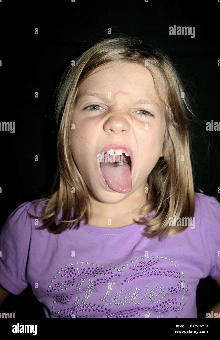 girl tongue girl,naughty,sticking out tongue,grimace - Stock Image