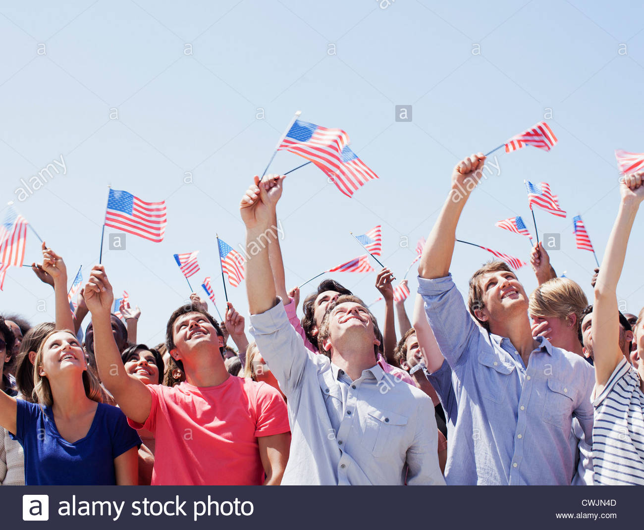 Smiling people waving American flags and looking up in ...