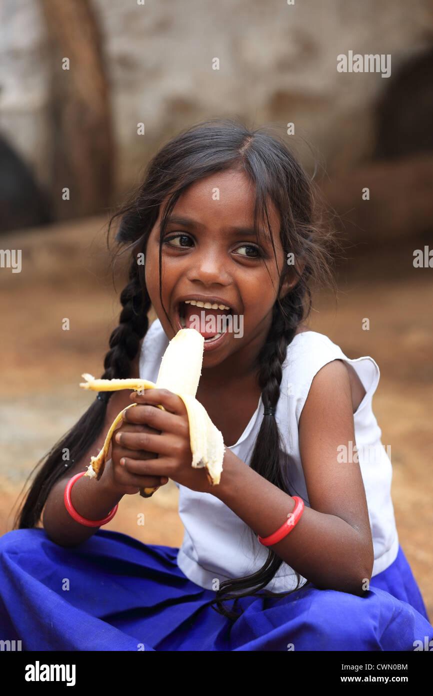 girls eating bannana Young Indian rural girl eating a banana Andhra Pradesh South India - Stock  Image