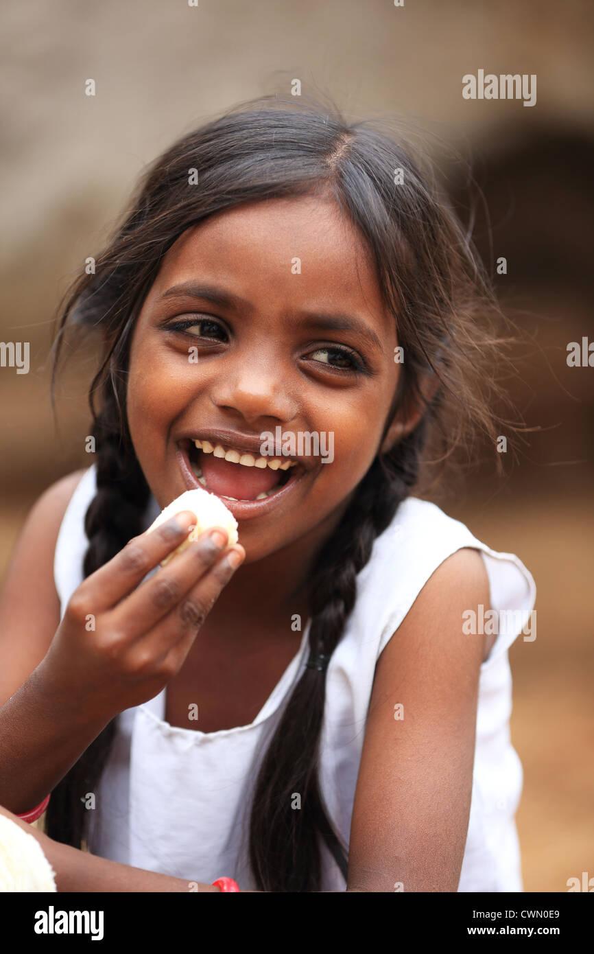 girls eating bannana Stock Photo - Young Indian rural girl eating a banana Andhra Pradesh South  India