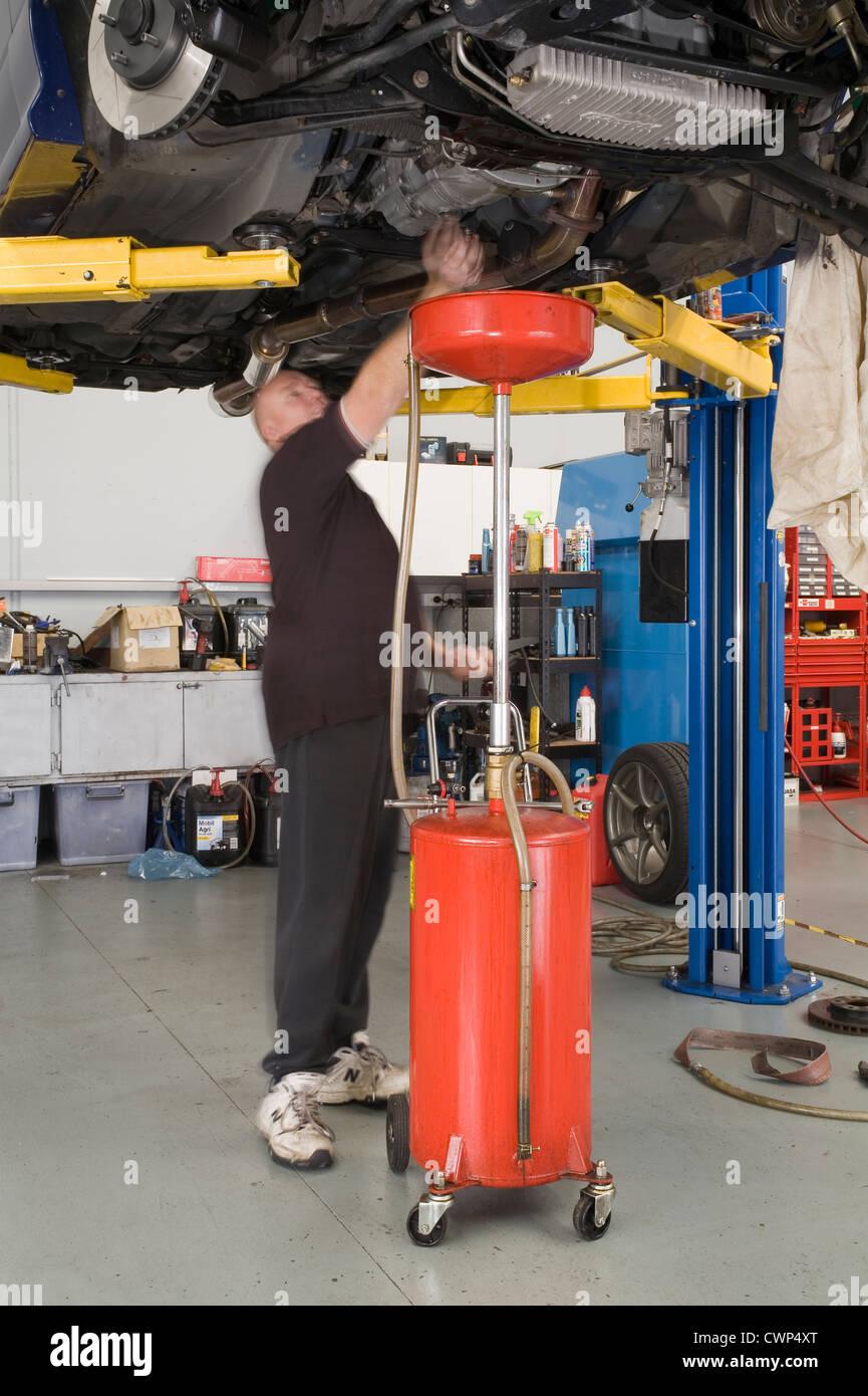 car mechanic working in a garage workshop changing the oil in a car mechanic working in a garage workshop changing the oil in a gearbox