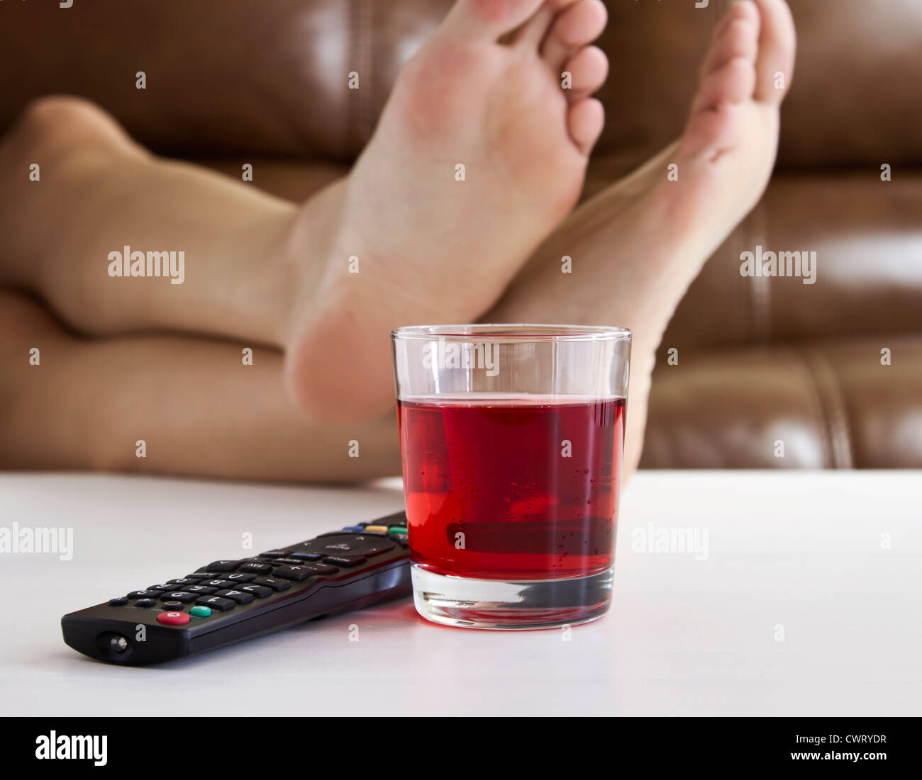 Persons feet up on coffee table while watching tv with remote persons feet up on coffee table while watching tv with remote control and drink on table geotapseo Gallery