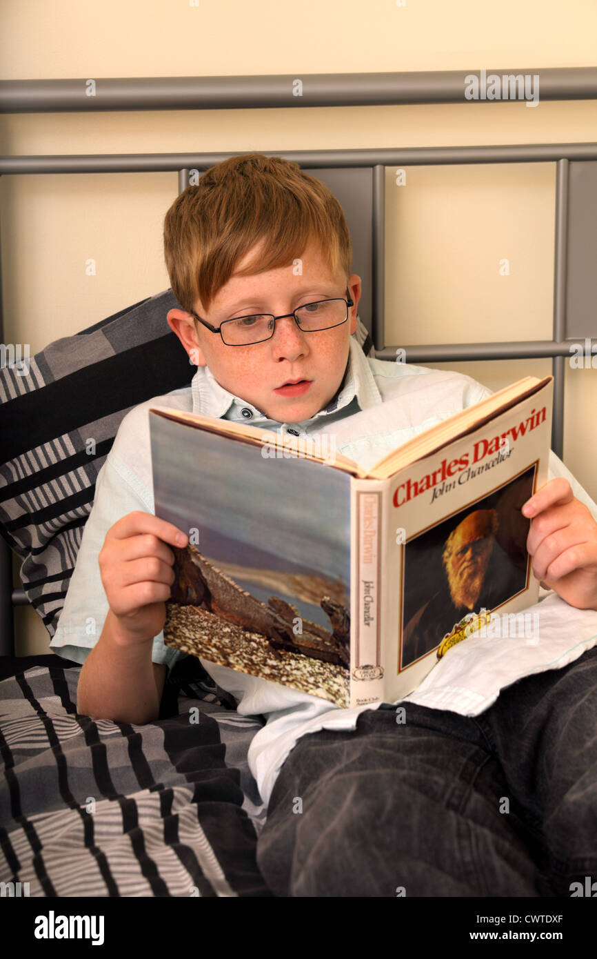 Beds For 13 Year Olds a 13 year old boy sitting on his bed reading a book about charles