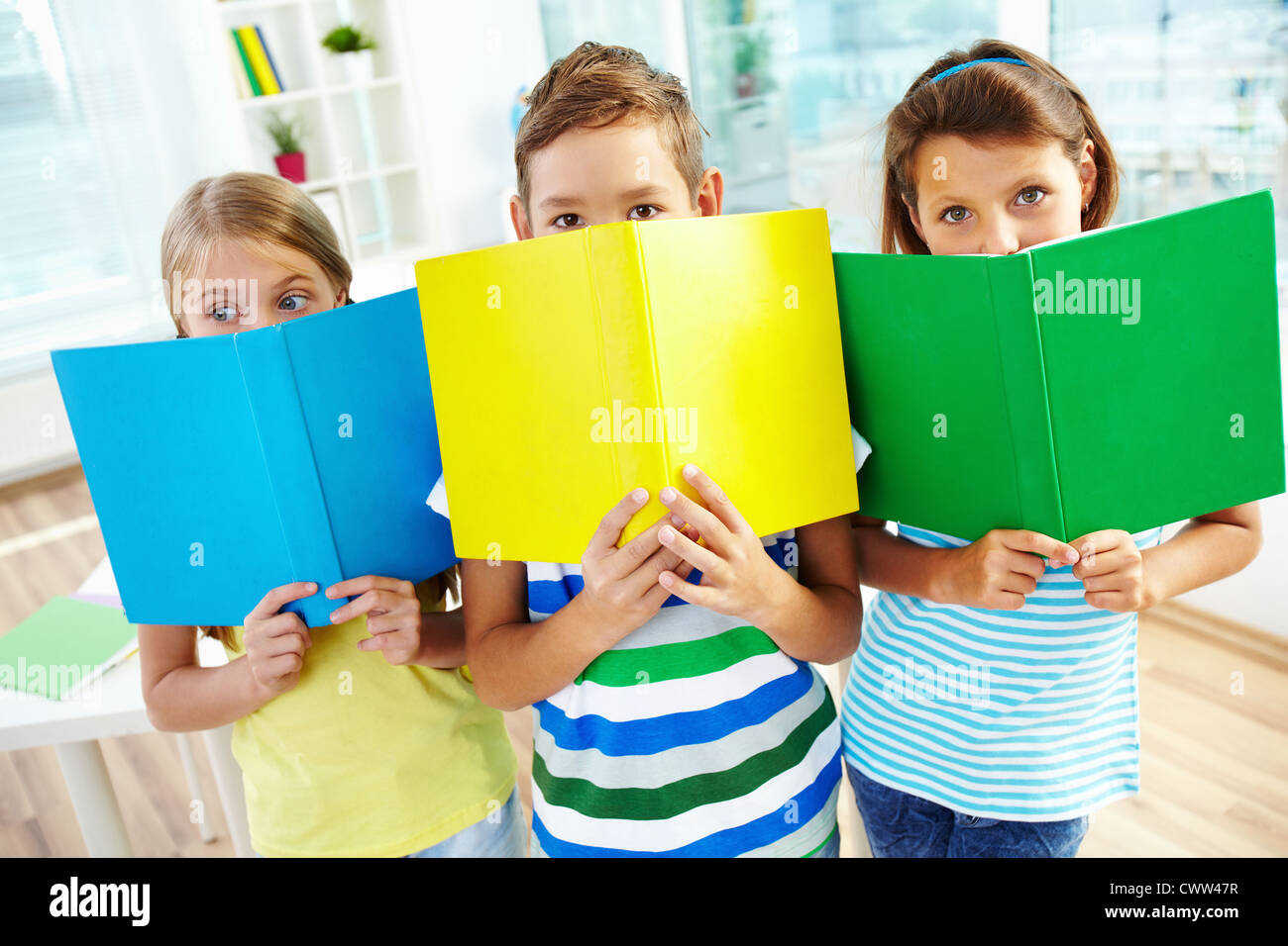 portrait of happy classmates with books looking at in stock