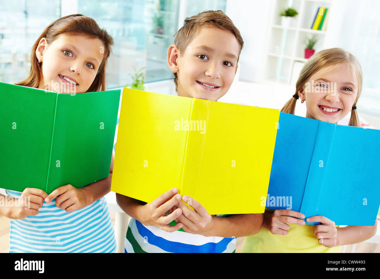 portrait of happy classmates with books smiling at in stock