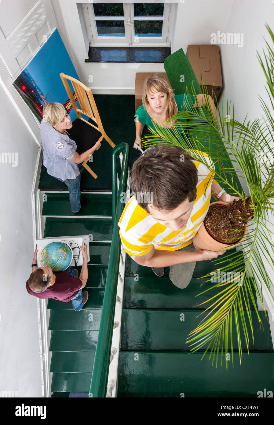 Young people moving in to a new apartment  Friends help carrying moving  boxes  furniture. Move Furniture Stairs Stock Photos   Move Furniture Stairs Stock