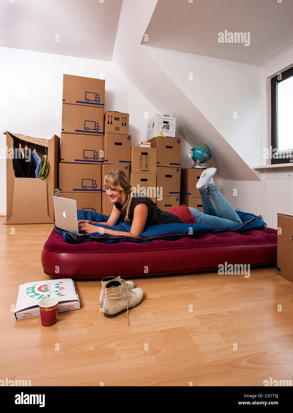 furniture for new apartment. stock photo young woman in her new apartment still no furniture living out of moving boxes works with laptop computer for