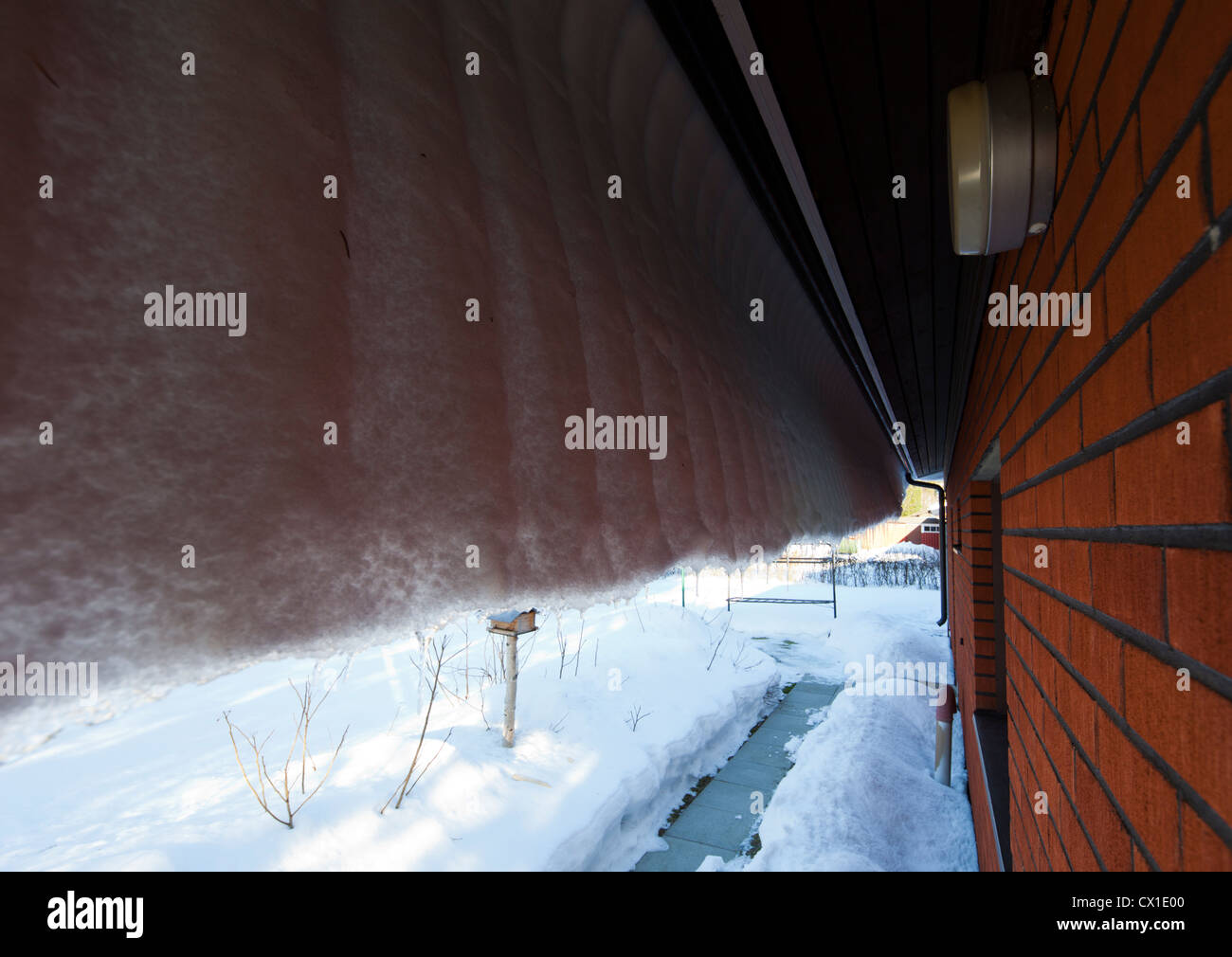 Snow And Ice Hanging Over House Roof Eaves Stock Photo