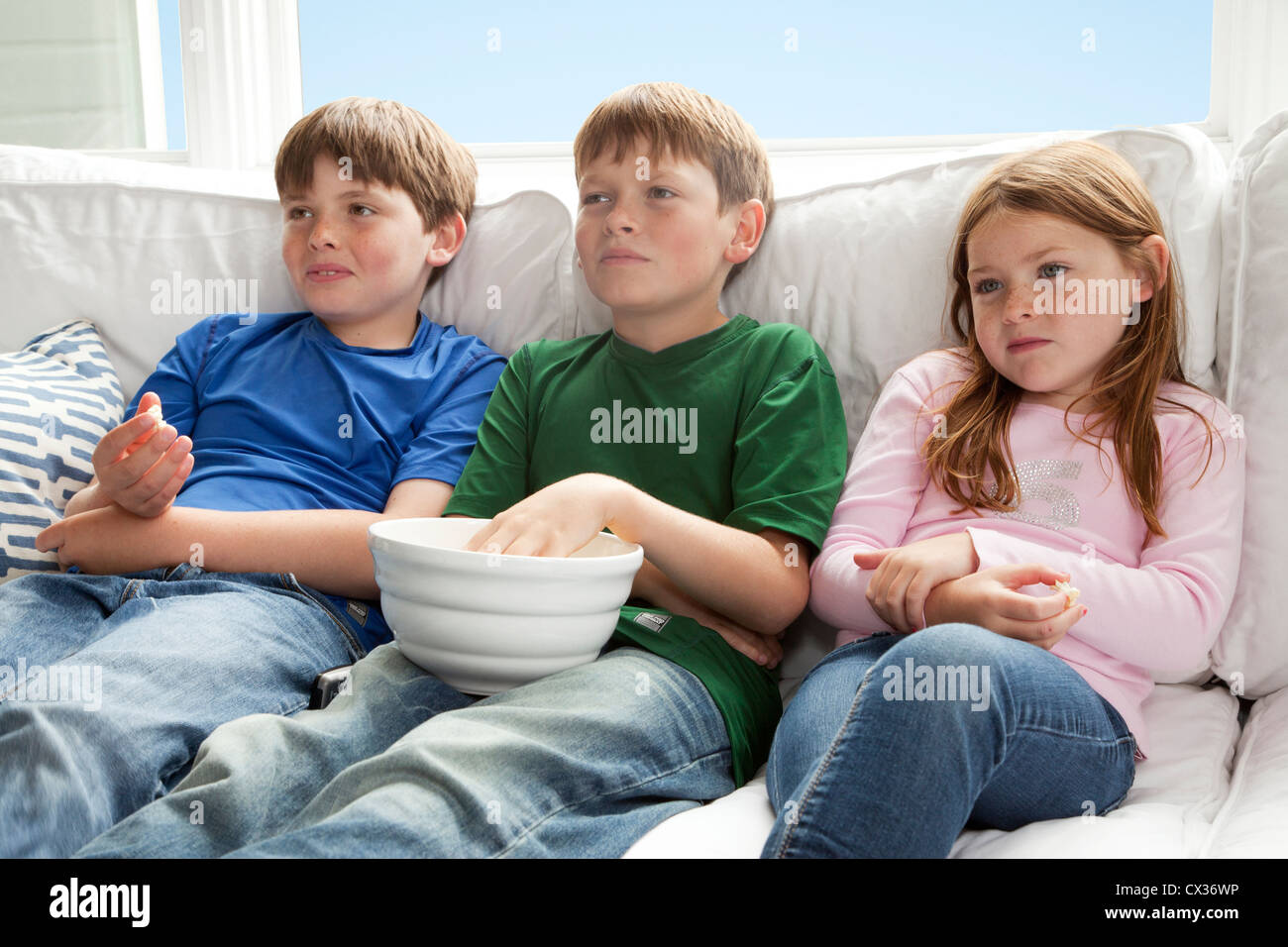 Three kids are sitting on the couch watching tv and eating for 3 on a couch