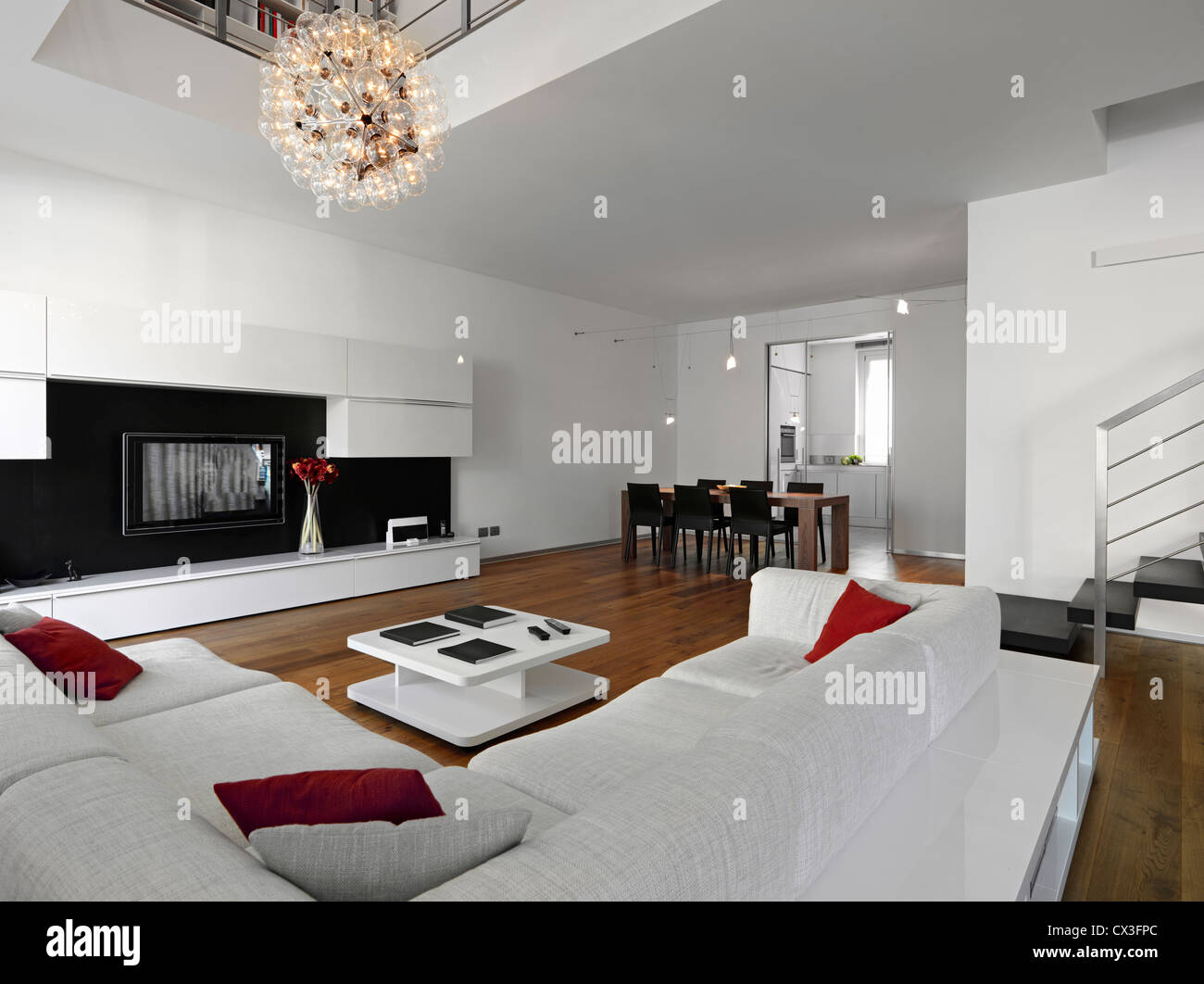 Modern Living Room Overlooking On Dining Table And Kitchen With Wood Floor