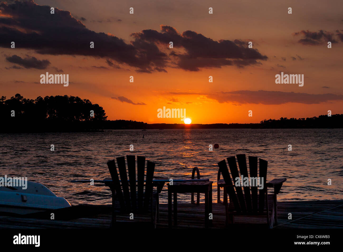 Beach chairs sunrise - Silhouettes Of Beach Chairs At Sunset On Lake Conroe Stock Photo