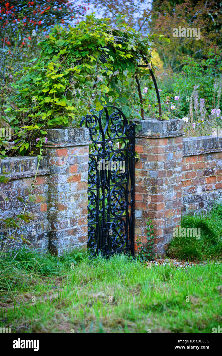 Garden Gate And Arch With Old Red Brick Wall And Green Vine, Red Berries And