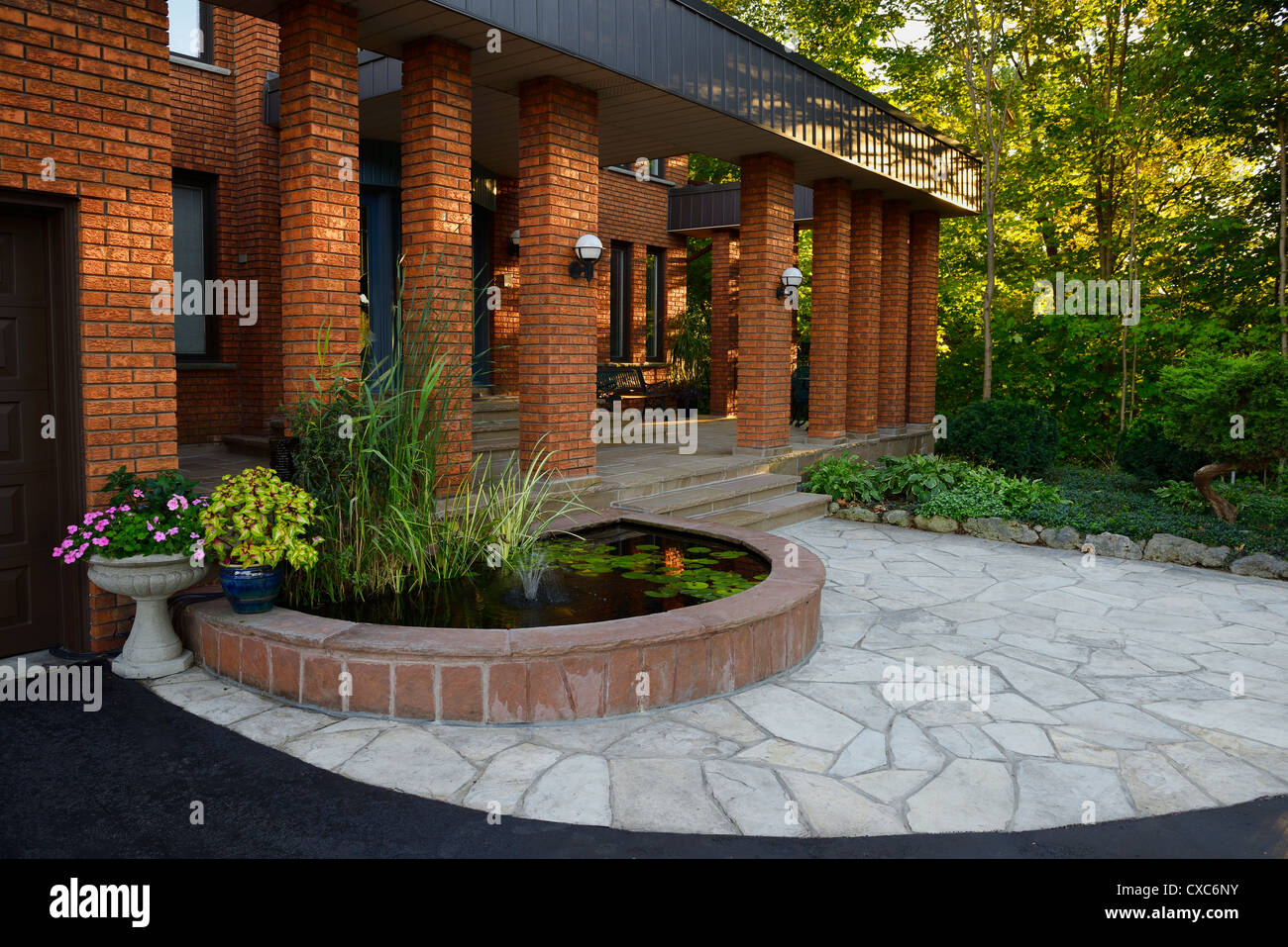 front entrance with pond and stone veranda on red brick house with