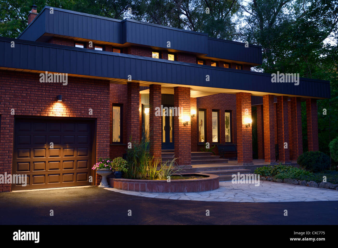 Front of a red brick house with lights on at twilight with pond and stone  porch Toronto Ontario Canada