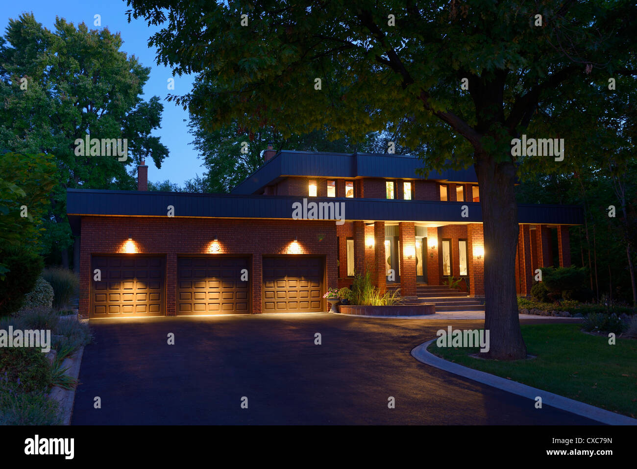 Twilight House red brick house with circular driveway and three car garage at