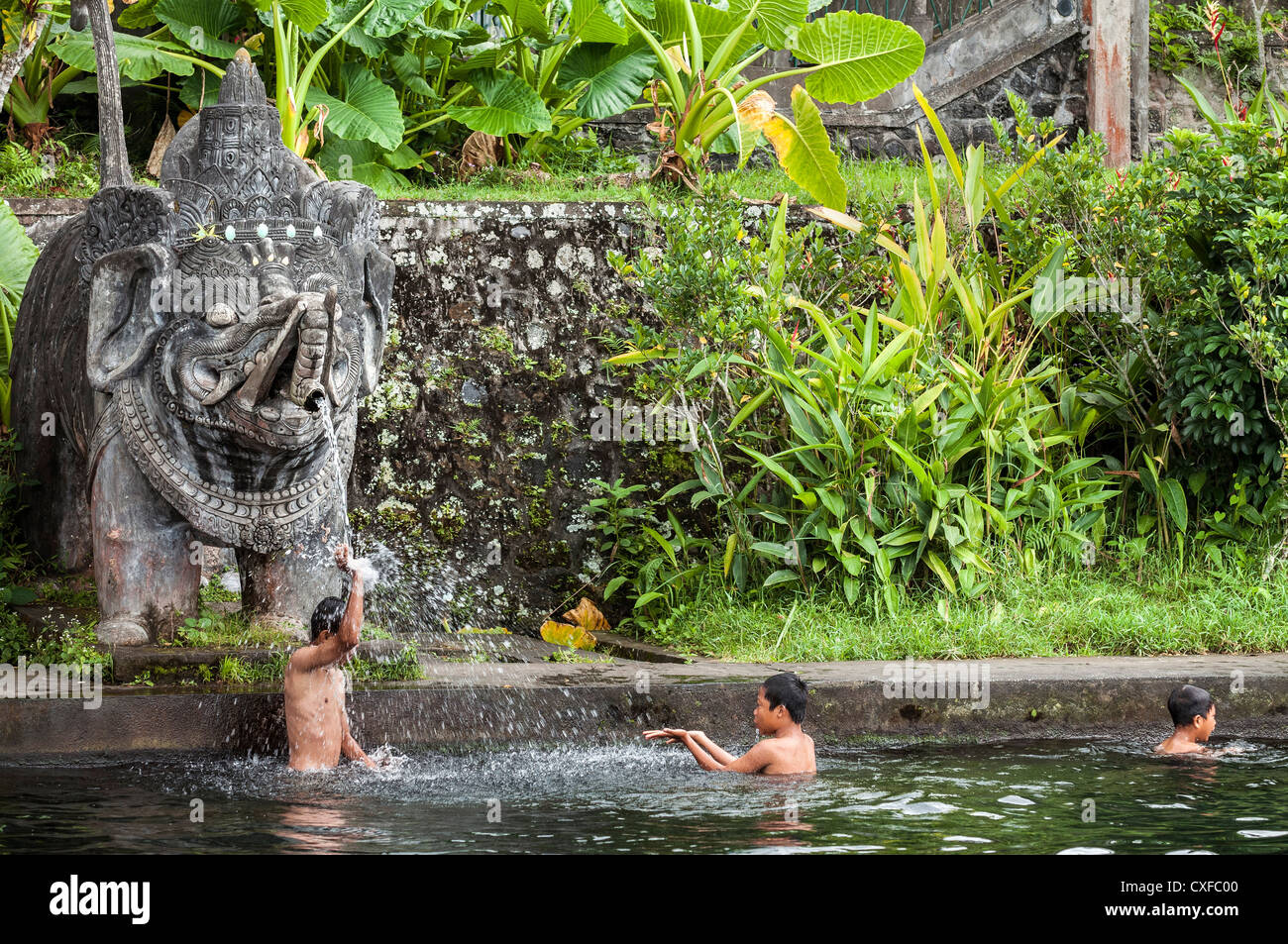 Children Swim By A Statue Of Hindu God Ganesh In A Pool At The Taman  Tirtagangga Water Palace And Garden, East, Bali, Indonesia.