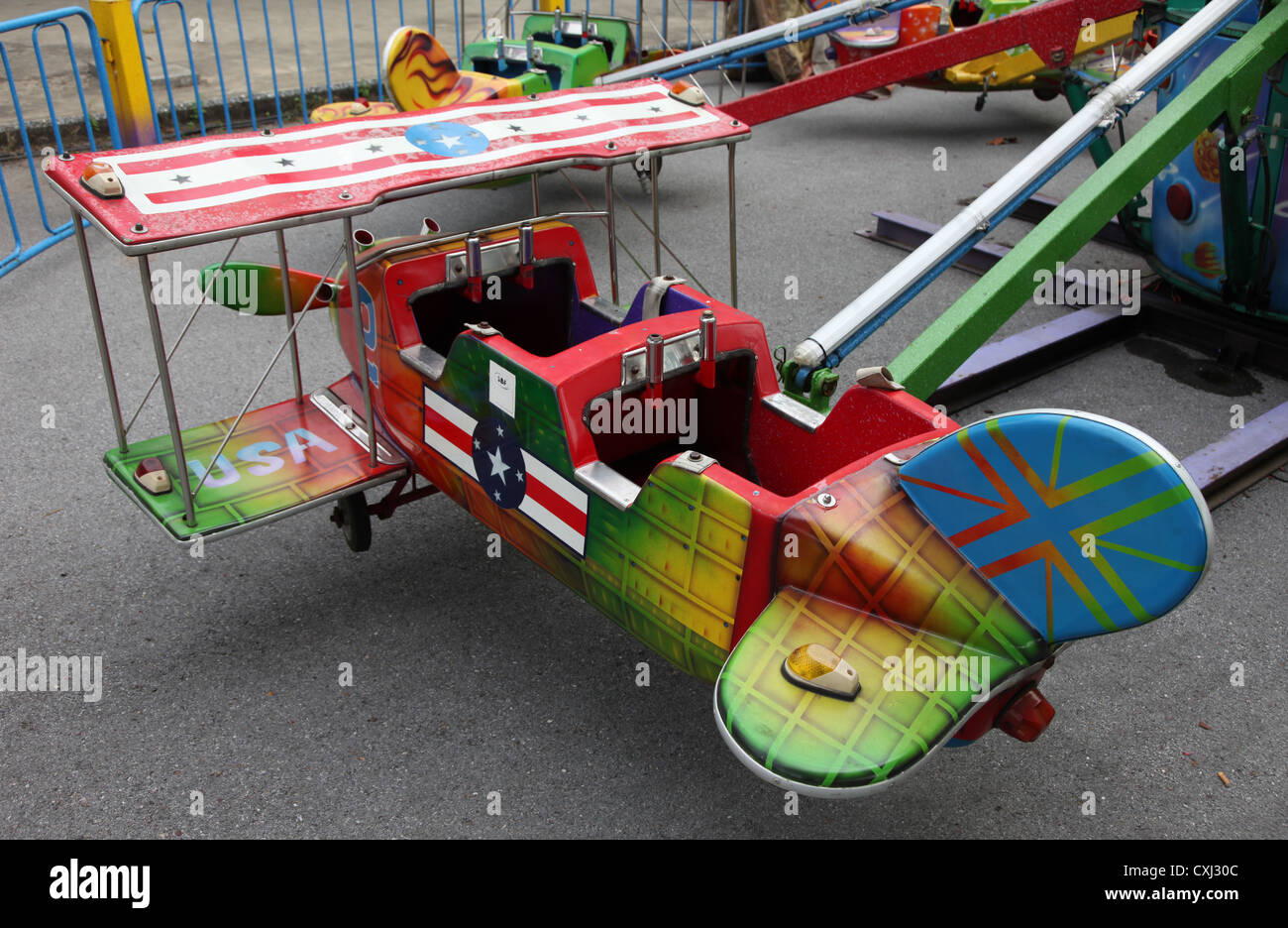 its a photo of toy planes in an entertainment park they are colorful small airplane for kids to play in old style look