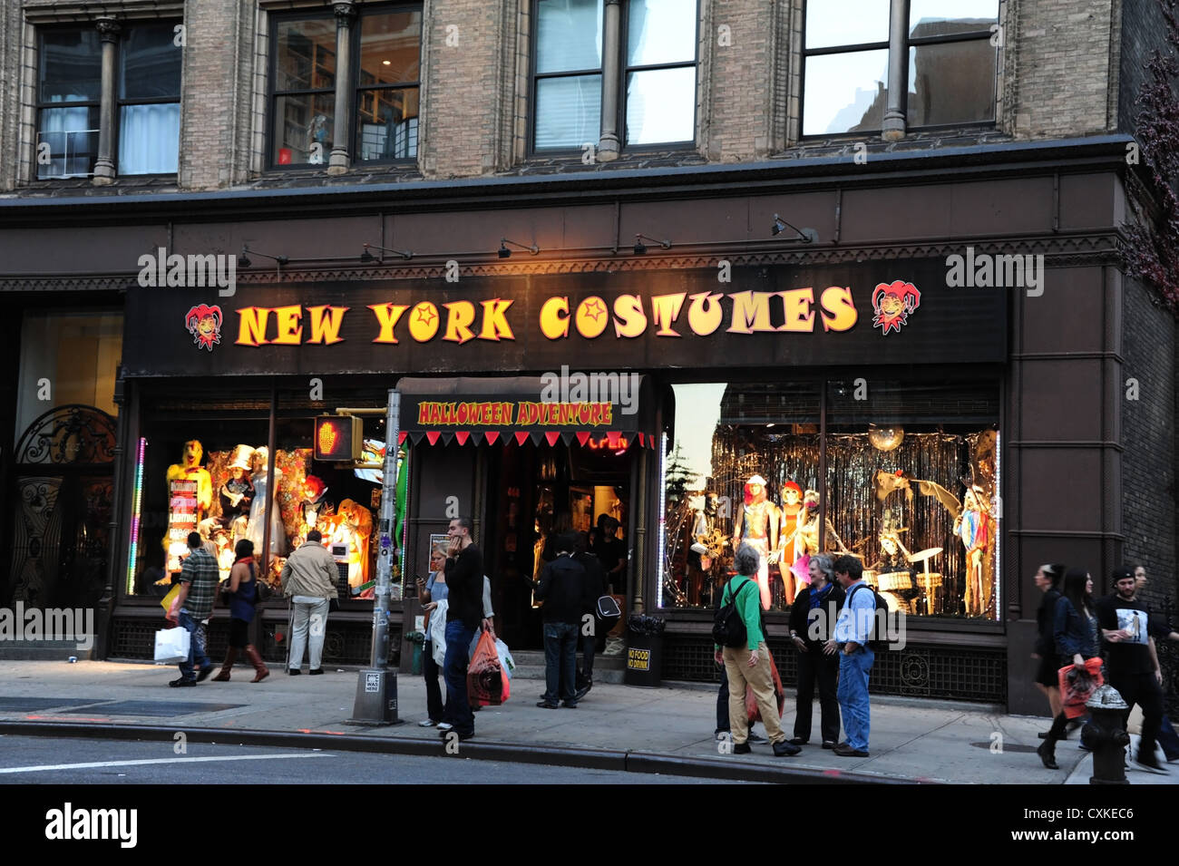 evening twilight view sidewalk people front halloween electric lights windows new york costumes store 808 broadway new york - Halloween Stores Ny