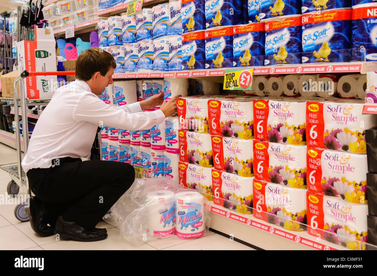 Store Manager Assists In Stacking Shelves In A Poundland