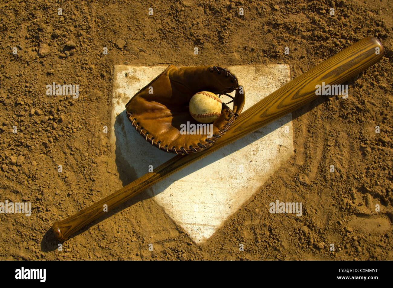 vintage wooden baseball bat glove and baseball on home plate