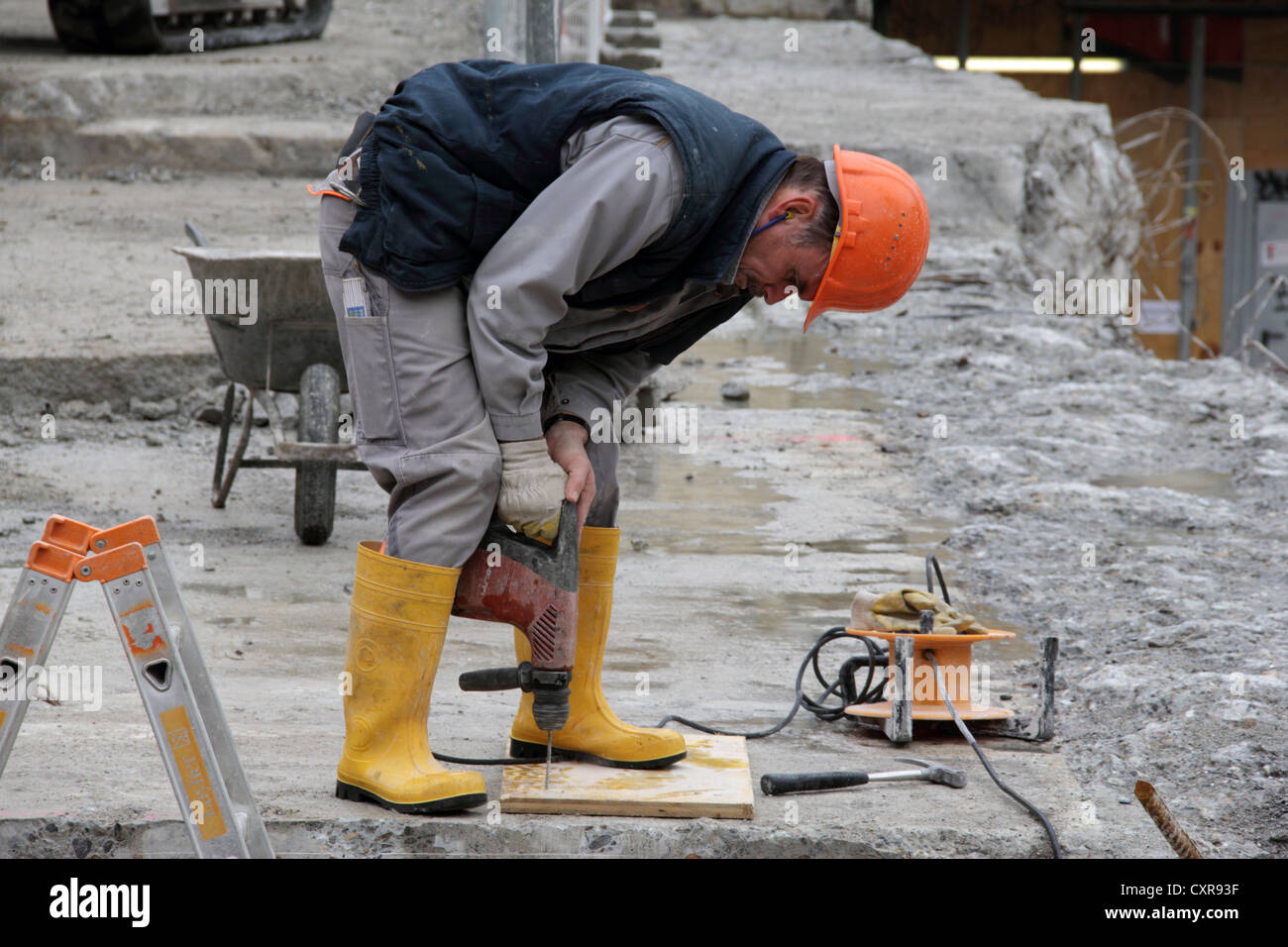 Construction worker drilling a hole into a concrete slab ...  Construction wo...