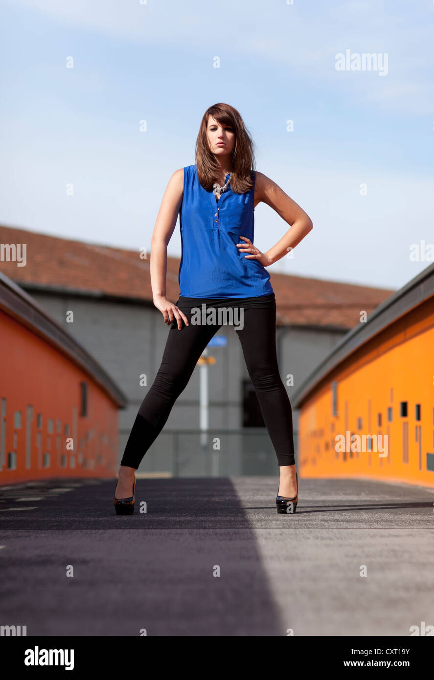 Young woman wearing a blue top, black leggings and high ...