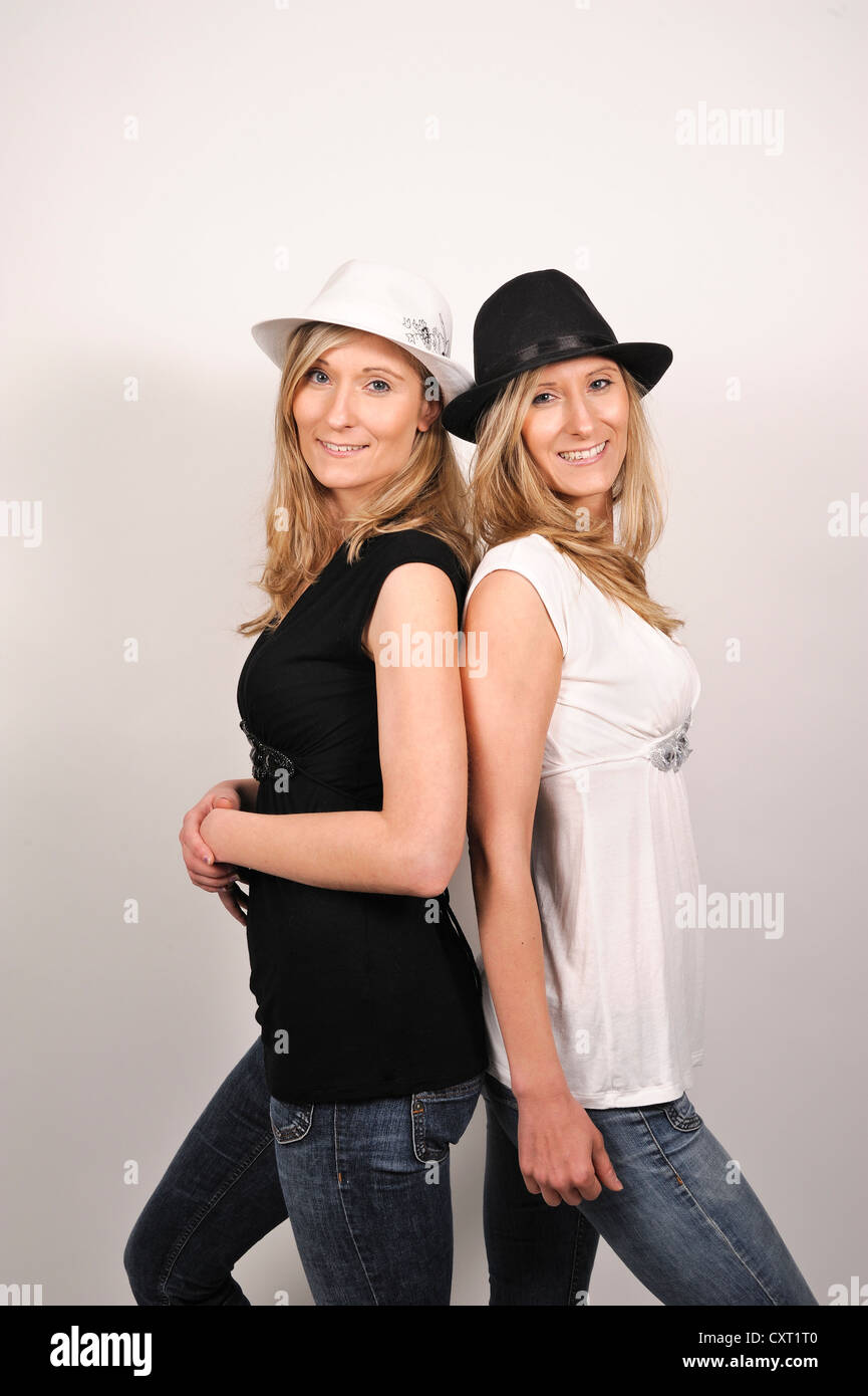 Twin Sisters Wearing Hats In Black And White Opposite Colors To Their Clothes
