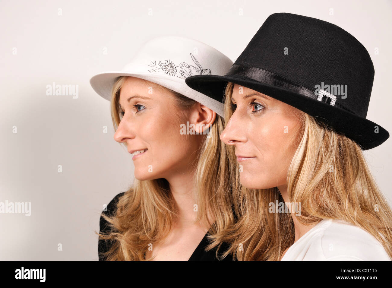 twin sisters wearing hats in black and white in opposite colors to