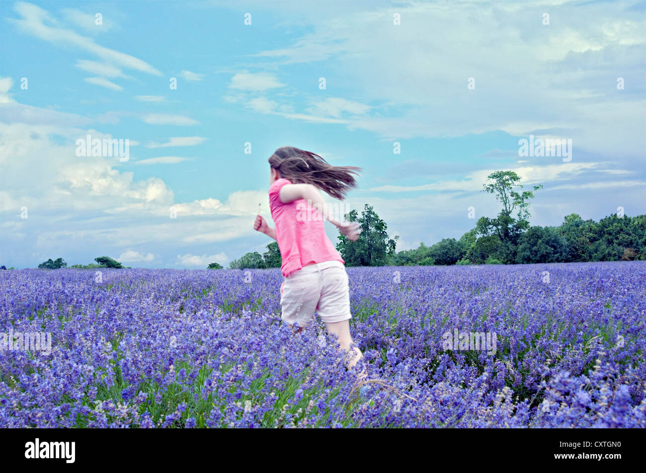 Girl running in field of flowers Stock Photo, Royalty Free ...