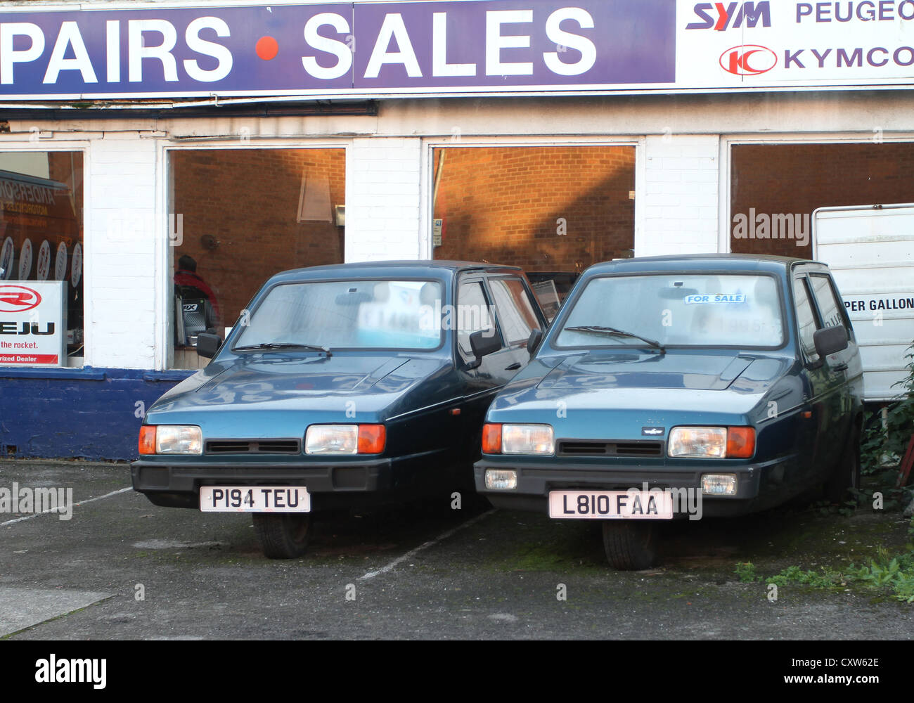 Two old three wheeled cars for sale on a garage forecourt in Stock ...