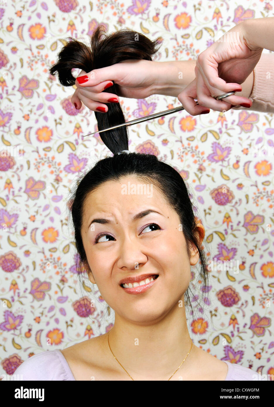 A Fearful Woman Having Her Ponytail Cut Off Stock Photo