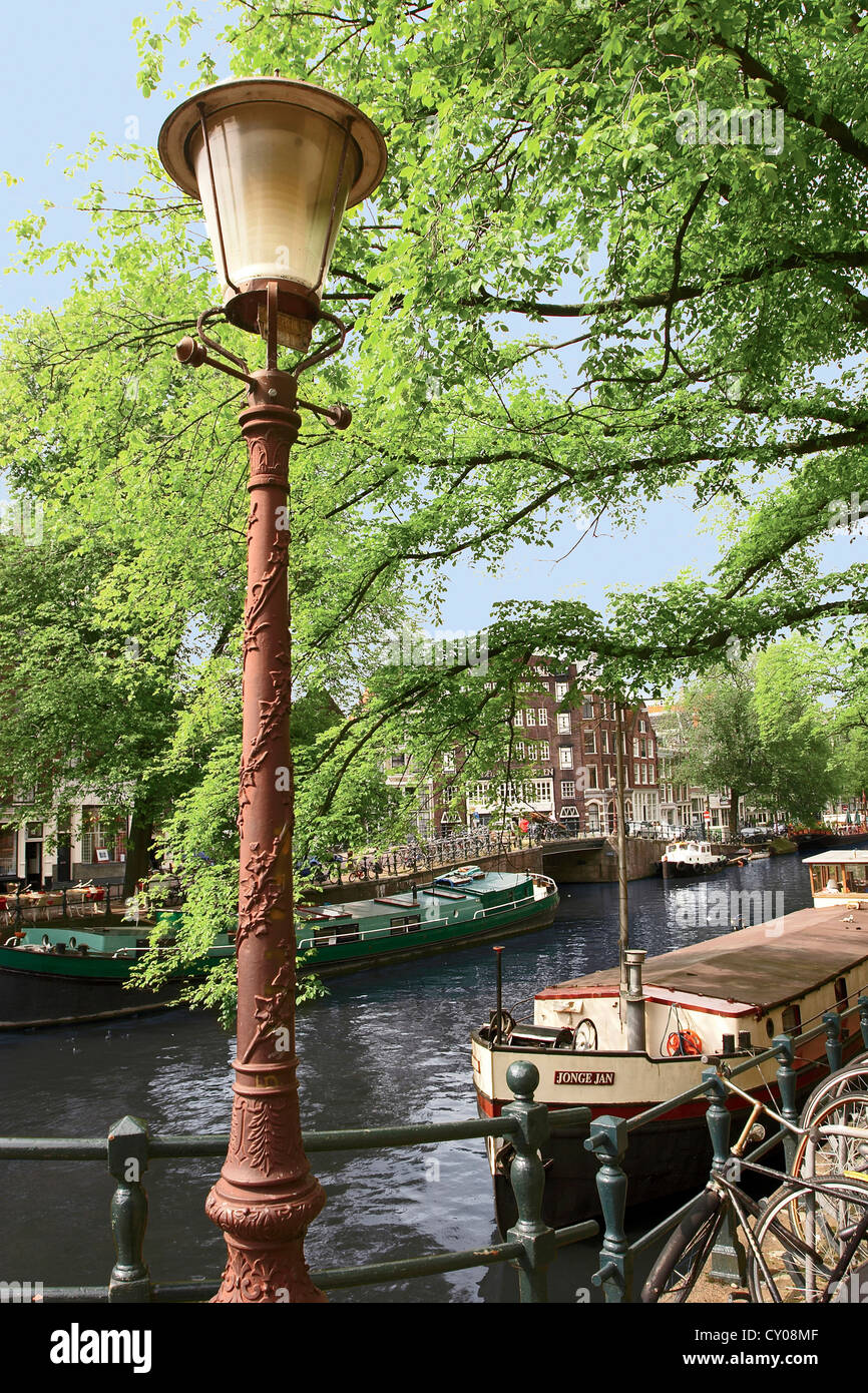 Amsterdam, Holland, Old Gas Lamp Post And Bicycles On A Bridge Over A Canal  In The Netherlands