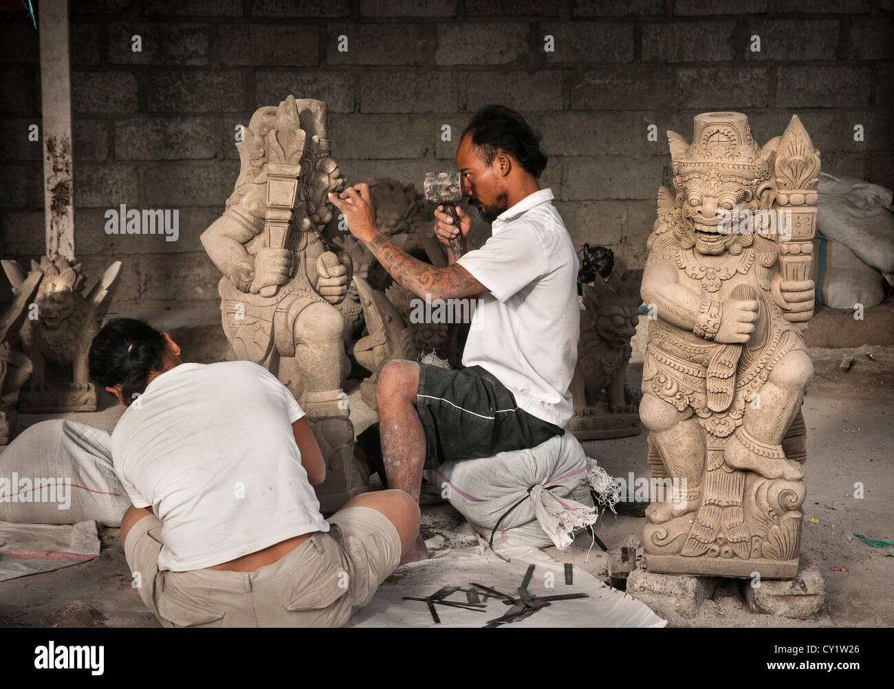 Stone mason carving a religious statue near ubud central