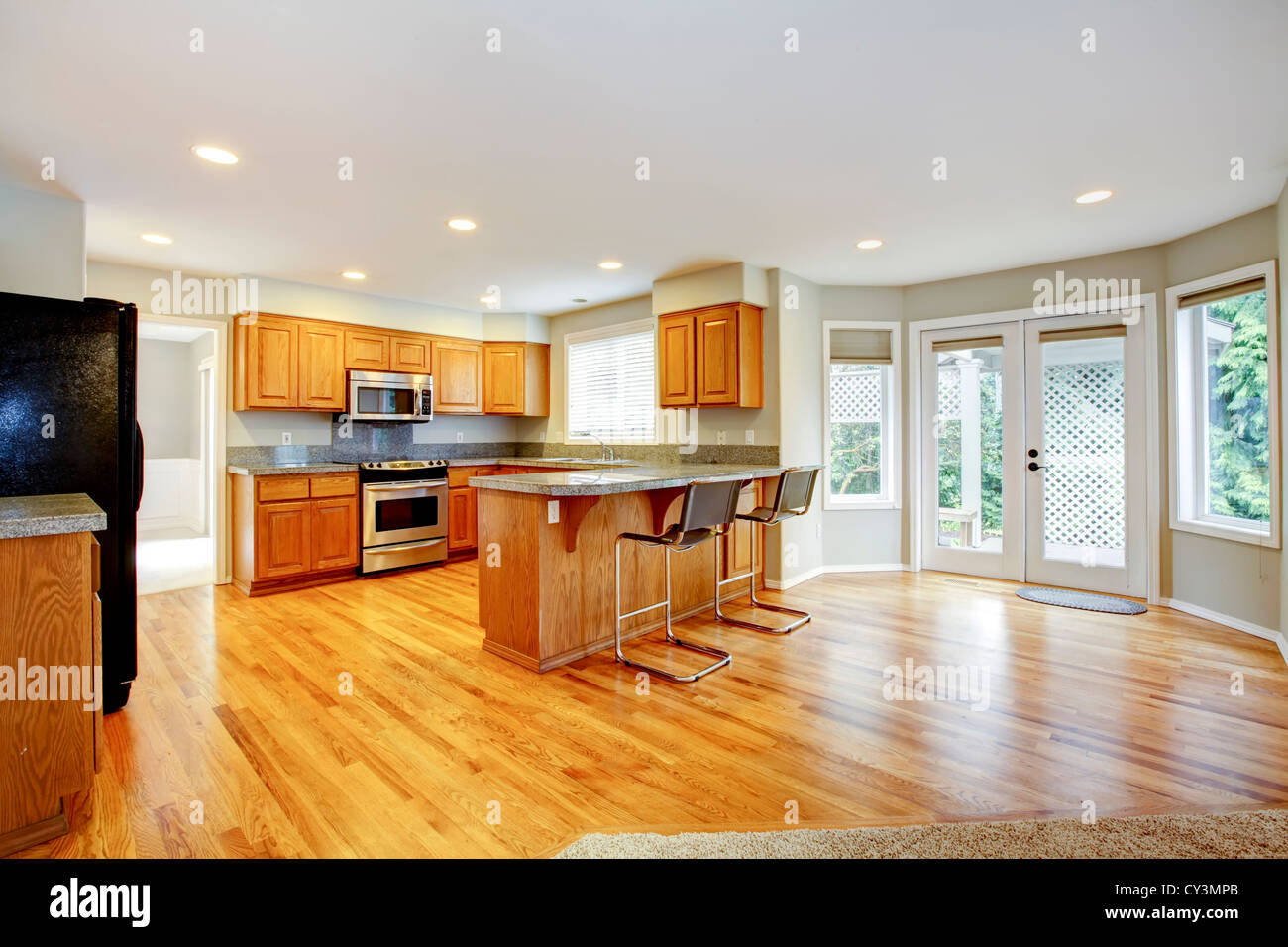 large empty open kitchen with living room with balcony doors and