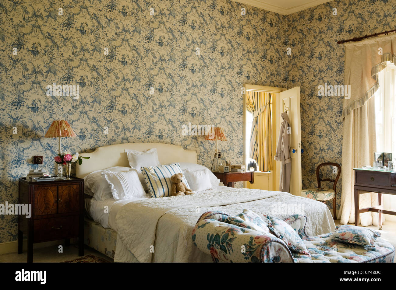 Toile de jouy wallpaper in bedroom with floral patterned chaise Stock Royalty Free Image