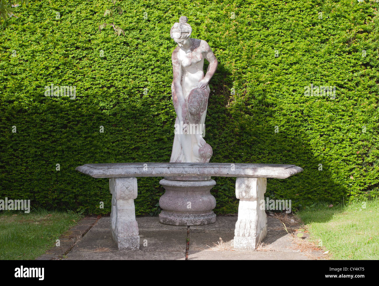 A Stone Statue And Bench Sit In An English Country Garden In Front Of A  Green Hedge