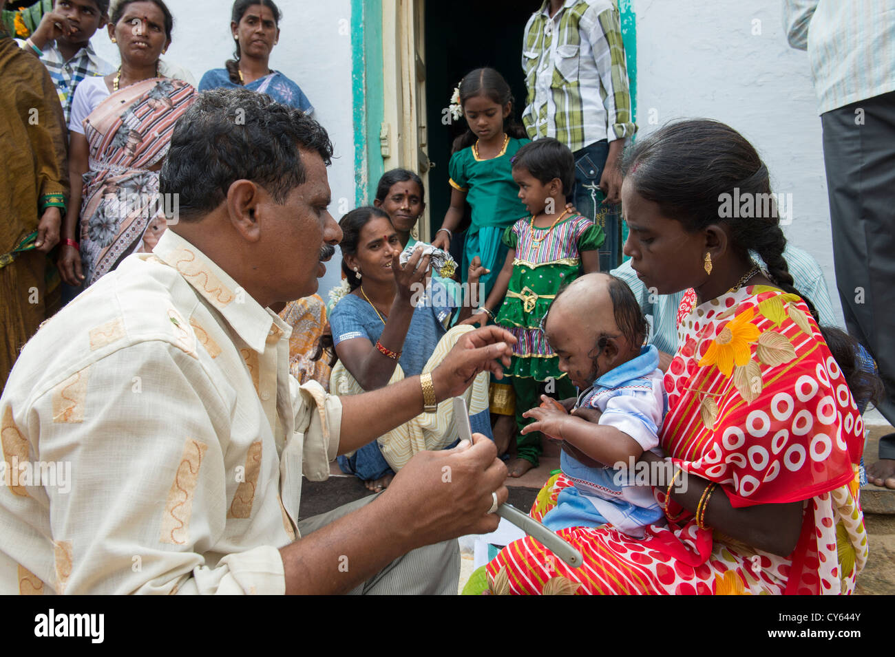 indian baby hair cutting ritual puja in a rural indian