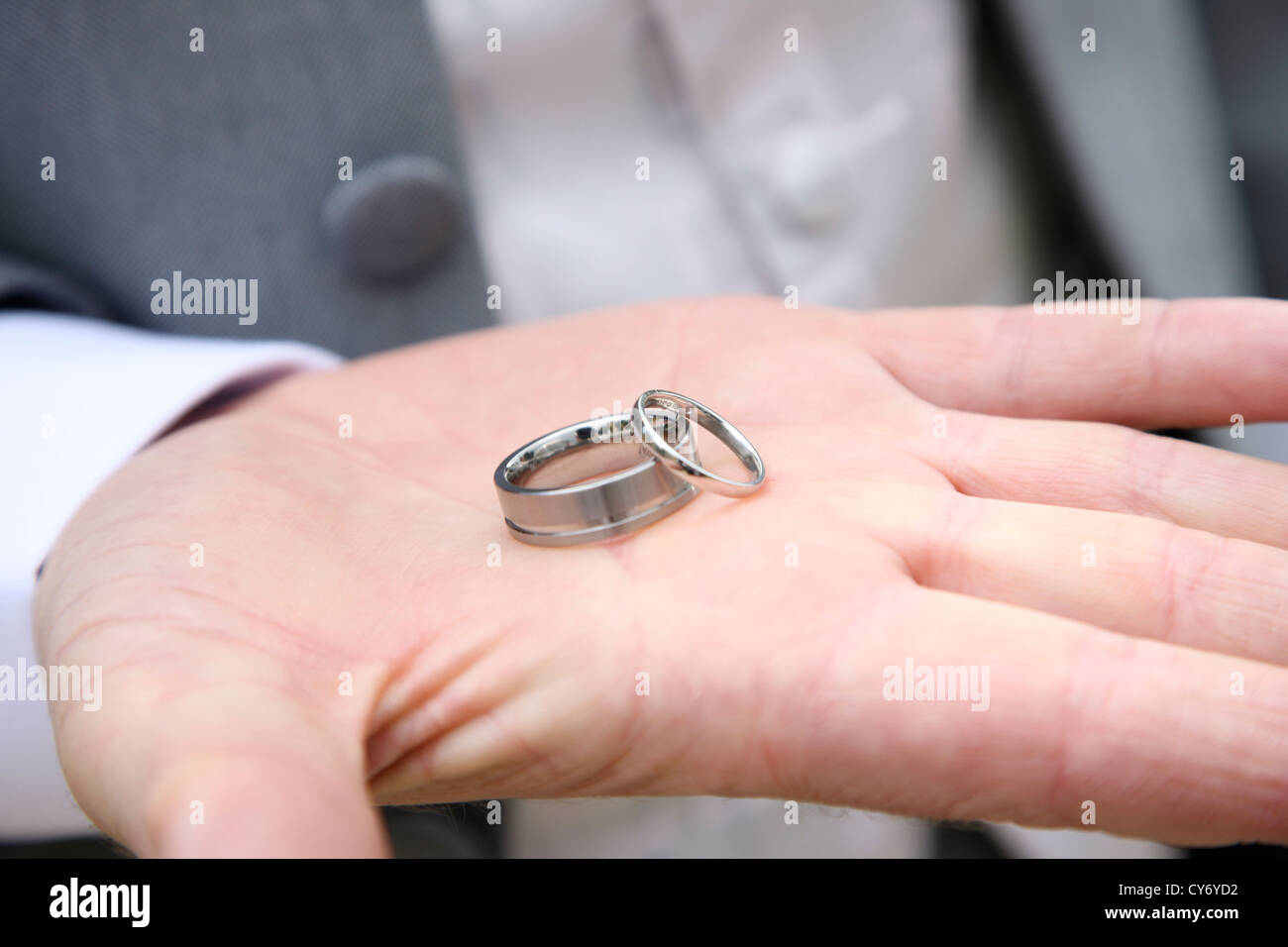 Bestman holding wedding rings in palm of hand on wedding day Stock