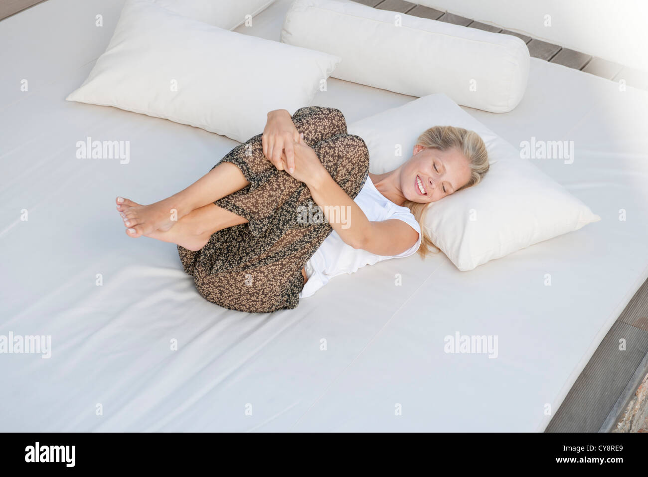 Young woman relaxing on bed in fetal position