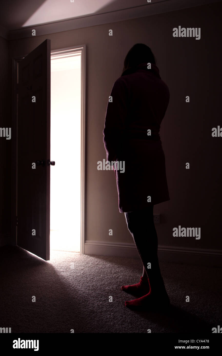 Back view of a teenage girl standing in a dark room looking