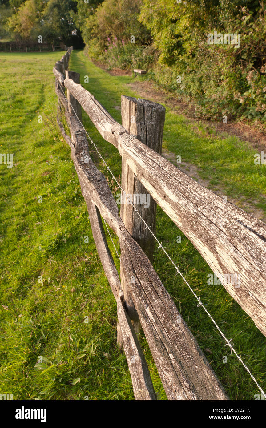 Weathered wooden split rail fence besides footpath with barbed stock photo weathered wooden split rail fence besides footpath with barbed wire in between rails posts to keep in cattle livestock to field baanklon Gallery