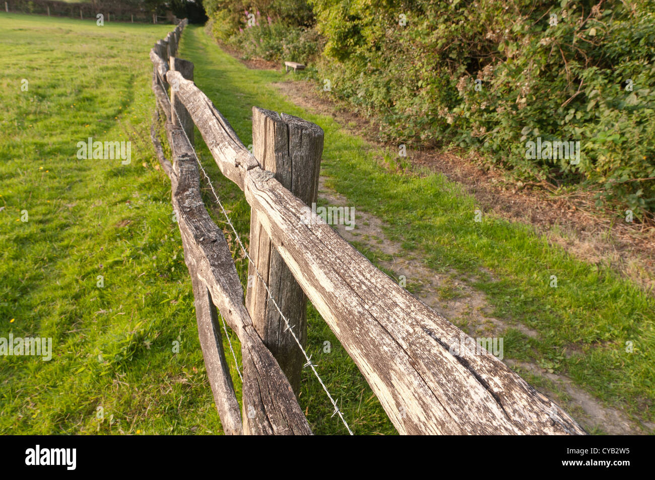 Log fence wood fence livestock weathered rustic stock photo weathered wooden split rail fence besides footpath with barbed wire in between rails posts to keep baanklon Gallery